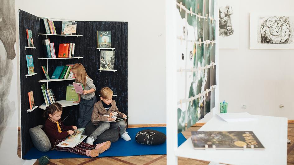 Lapsia kirjahyllyn edessä näyttelyssä